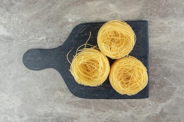 Nids de spaghetti minces sur planche de bois