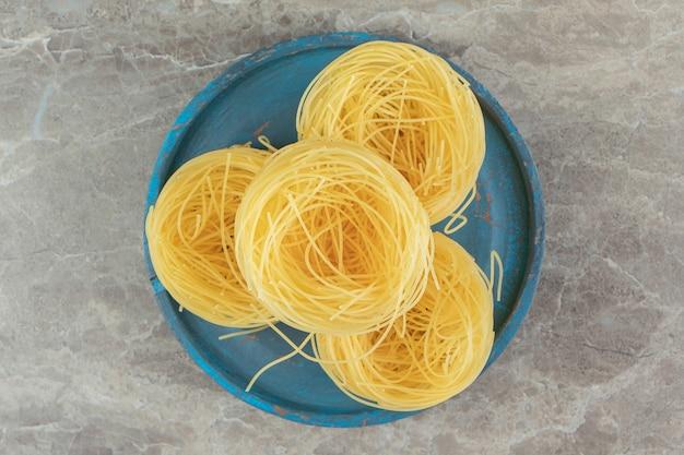 Nids de spaghettis crus sur plaque bleue