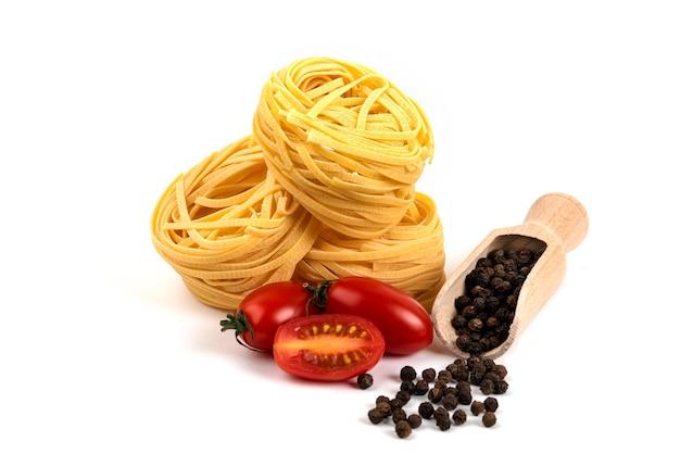 Nids de spaghettis crus, tomates et grains de pepepr sur blanc.