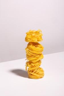 Nids de spaghettis non cuits disposés les uns sur les autres avec une ombre sur un fond clair. ingrédients pour la recette