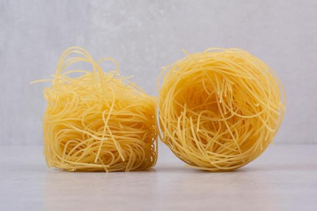 Nids de spaghettis non cuits sur table en marbre.