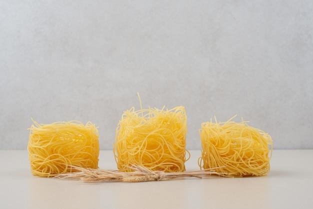 Nids de spaghettis secs sur une surface blanche avec du blé