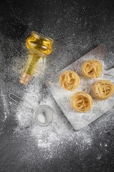 Nids de tagliatelles fraîches crues avec sur planche de bois avec bouteille d'huile