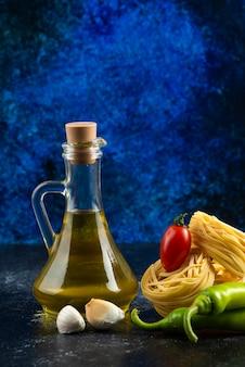 Nids de tagliatelles, huile et légumes sur table en marbre.