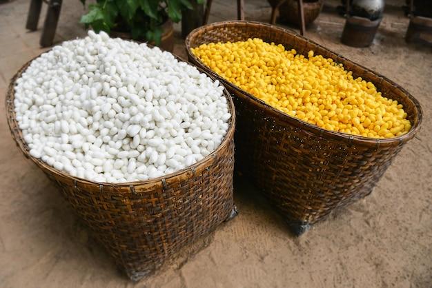 Nids de vers à soie dans le panier prêts à être transformés en textile de soie avec un faible éclairage extérieur.