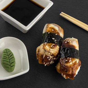 Nigiri sushi avec anguille au wasabi, sauce soja et bâtonnets de bambou servi sur ardoise en pierre noire, cuisine japonaise traditionnelle, fond de nourriture