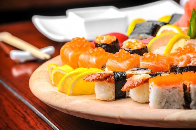 Nigiri sushi et petits pains au poisson servis sur une table en bois