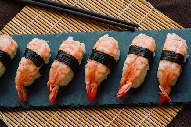 Nigiri sushi prêt à manger sur une ardoise avec des baguettes et un tapis roulant traditionnel en bambou