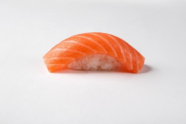 Nigiri sushi saumon isolé sur une surface blanche.