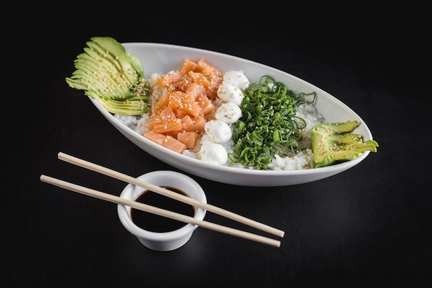 Nikkey gohan avec du riz blanc, du saumon, de l'avocat et du fromage de philadelphie sur un tableau noir