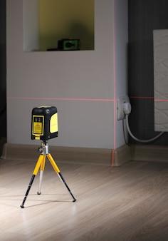 Le niveau laser de construction sur le mini trépied est au sol