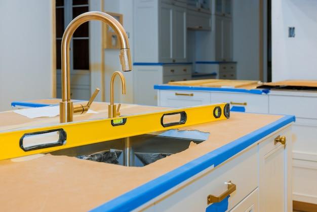 Niveler avec des comptoirs un évier dans la cuisine de rénovation de l'armoire