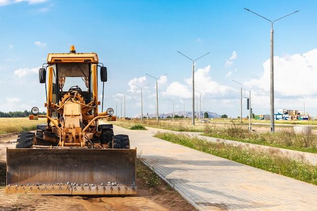 Niveleuse - équipement lourd pour la construction de routes et les travaux de terrassement. nivellement et amélioration de la surface du sol. construction de routes et de communications de transport.