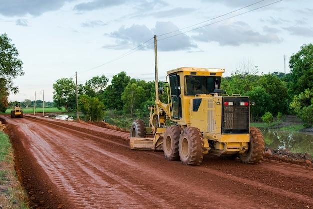 Niveleuse jaune route travaillant sur le chantier de construction de la nouvelle route.