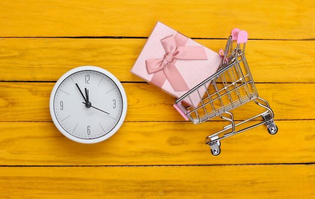 Noël, achats du nouvel an. chariot de supermarché mini avec boîte-cadeau et horloge sur une surface en bois jaune. vue de dessus