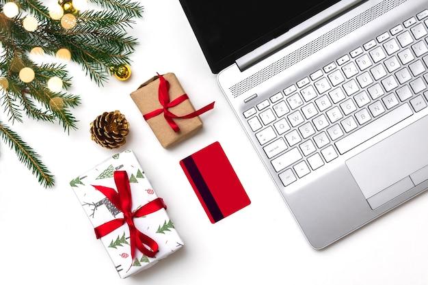 Noël achats en ligne à plat. un ordinateur portable ouvert, une carte de crédit, des coffrets cadeaux noués d'un ruban rouge, des branches de sapin vert, des guirlandes d'étoiles