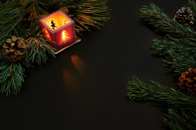 Noël, arbre de noël, bougie, cônes et bâtons de cannelle sur fond noir. vue de dessus. espace de copie. nature morte. mise à plat. nouvelle année