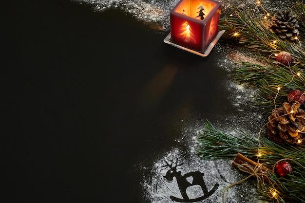 Noël, arbre de noël, bougie, neige, cônes et bâtons de cannelle sur fond noir. vue de dessus. espace de copie. nature morte. mise à plat nouvel an