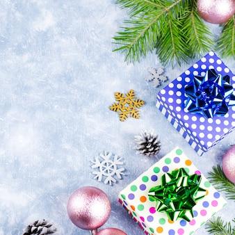 Noël bleu avec des branches de sapin, des coffrets cadeaux, des décorations argentées et dorées, espace copie. vue de dessus