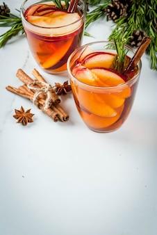 Noël, boissons de thanksgiving. automne, cocktail grog d'hiver, sangria chaude, vin chaud - pomme, romarin, cannelle, anis. sur table en marbre blanc. avec cônes, romarin. espace copie