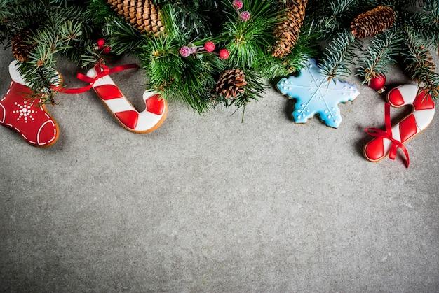 Noël avec une branche de sapin, des biscuits de pain d'épice colorés faits maison, des pommes de pin et des décorations sur une table en pierre grise. vue de dessus, copyspace