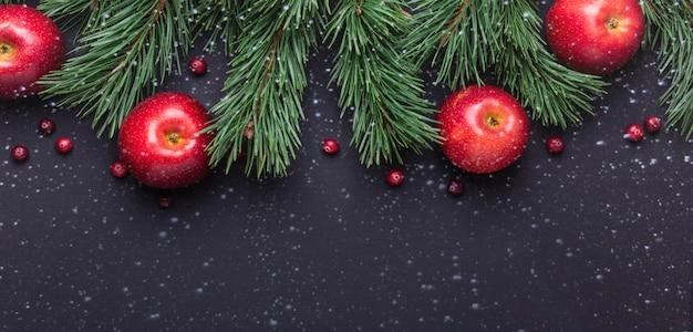Noël avec des branches d'arbres, des pommes rouges et des canneberges effet de dessin de neige