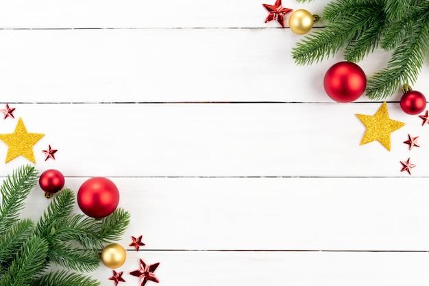 Noël avec des branches d'épinette, boule rouge et étoile sur fond en bois.