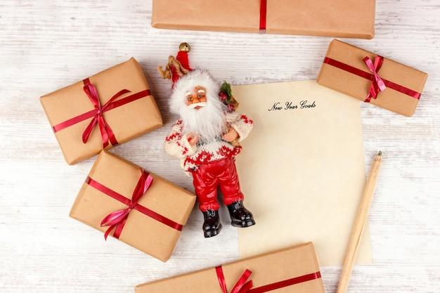 Noël avec des coffrets cadeaux, le père noël et une feuille de papier avec des objectifs de nouvel an