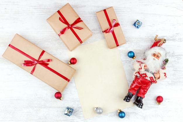 Noël avec des coffrets cadeaux, le père noël et une feuille de papier sur une table en bois blanc