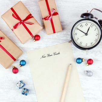 Noël avec des coffrets cadeaux, réveil, boules de décoration de noël et feuille de papier sur une table en bois blanc