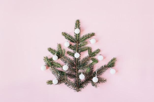 Noël, composition du nouvel an. sapin de noël fait de branches de sapin et décoré de boules sur rose