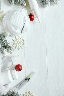 Noël coronavirus médical à plat, masque protecteur, pilules, antiseptiques, thème du nouvel an vue de dessus, minimalisme, mise en page à plat, concept de covid et bonne année.