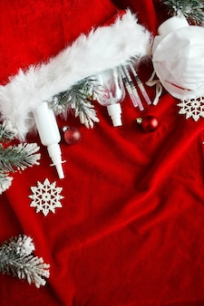 Noël coronavirus médical à plat, masque de protection, pilules, antiseptiques, décoration sur fond rouge, thème du nouvel an vue de dessus, minimalisme, mise en page à plat, concept de covid et bonne année