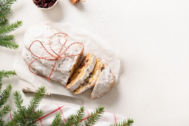 Noël coupé stollen avec des fruits confits sur table blanche. délicieuses friandises traditionnelles allemandes. copiez l'espace.