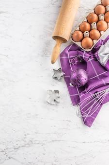 Noël cuisson cadeaux violets décorations oeufs et ustensiles de cuisine sur table en marbre.