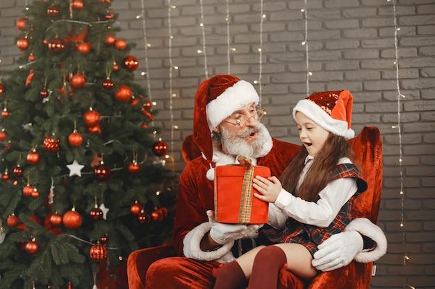 Noël, enfant et cadeaux. le père noël a apporté des cadeaux à l'enfant. joyeuse petite fille étreignant le père noël.
