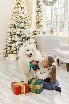 Noël enfant fille câlin chien samoyède. concept de noël, d'hiver et de personnes. carte de voeux de noël. bonne année. nouvel an à la maison
