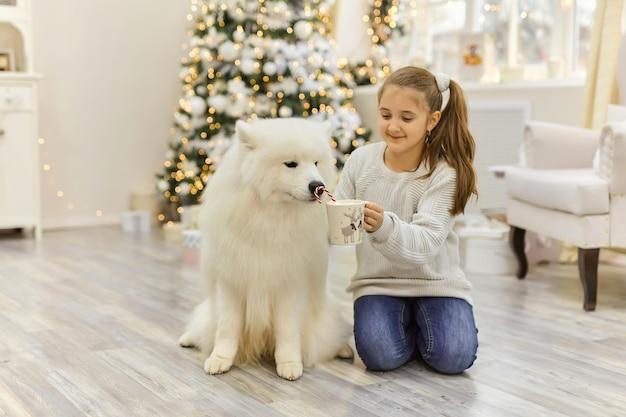 Noël enfant fille câlin chien samoyède. concept de noël, d'hiver et de personnes.