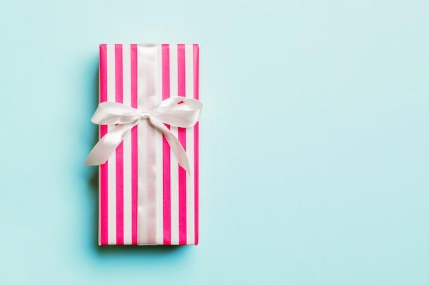 Noël enveloppé ou autre cadeau de vacances à la main en papier avec ruban blanc sur fond bleu