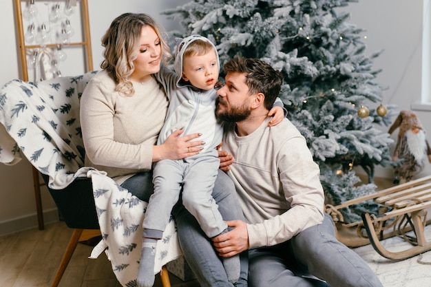 Noël famille bonheur portrait de papa, maman enceinte et petit-fils assis fauteuil à la maison près de l'arbre de noël câlin sourire européen jeune adulte matin de vacances en famille