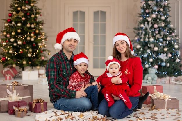 Noël en famille! heureuse maman, papa et petite fille et fils sur le chapeau du père noël