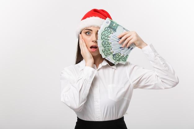 Noël et finance concept jeune femme d'affaires montrant de l'argent fermant son visage avec une expression de surprise