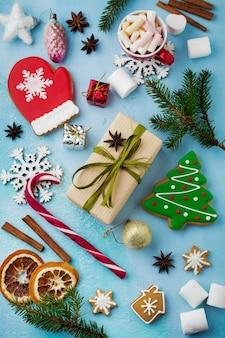 Noël. groupe de pains d'épices, cannelle, orange, jouets et tasse de chocolat chaud sur bleu clair.