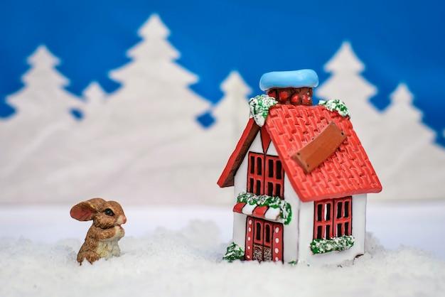 Noël d'hiver avec un lapin près de la maison