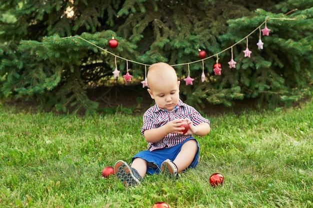 Noël en juillet, petit garçon à noël. tir en été dans le parc, décor du nouvel an