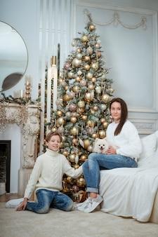 Noël à la maison fils et maman et chien sous un arbre un garçon et une femme jouent avec un animal célébrant...
