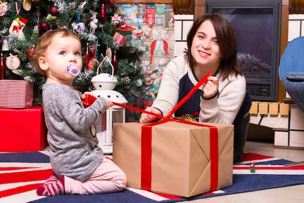 Noël, maman et fille ouvrent un cadeau à la maison