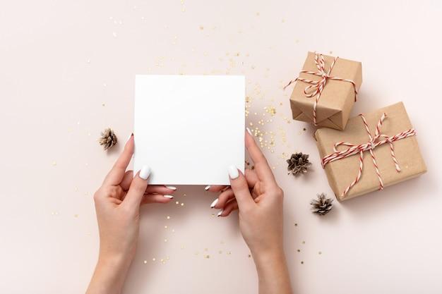 Noël. maquette de papier carré vierge, confettis d'étoiles dorées, bosses, coffrets cadeaux sur fond beige