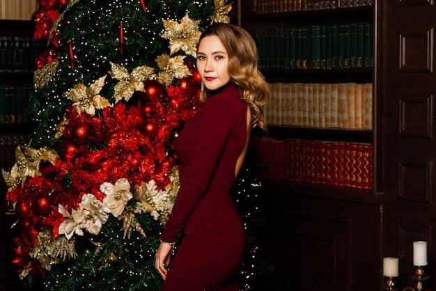 Noël, noël, hiver, concept de bonheur - femme souriante en vêtements de père noël avec de nombreux coffrets cadeaux