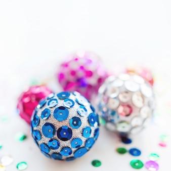 Noël et nouvel an avec des boules lumineuses. décorations à la main pour arbre de noël avec des paillettes scintillantes colorées.